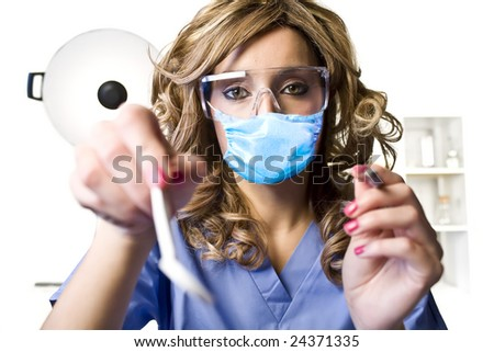 A young pretty dentist with tools getting ready to take a look - stock photo