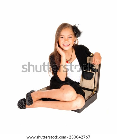 A young pretty eight year old girl sitting for white background in a briefcase, smiling, holding her hand o her face, isolated over white.  - stock photo