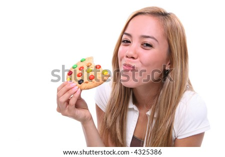 A young pretty girl eating a chocolate chip cookie dessert - stock photo