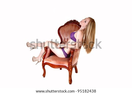 A young pretty woman in lingerie sitting in a pink old armchair with her legs over the side and her long blond hair hanging down, over white. - stock photo
