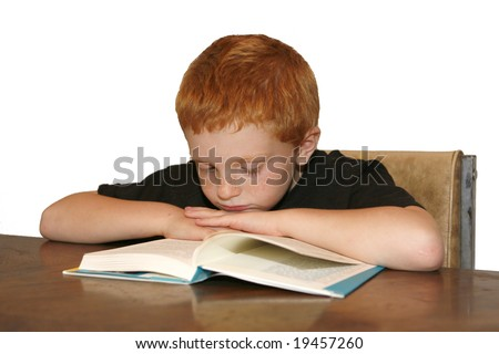 A young red haired boy falling asleep while reading a book. - stock photo