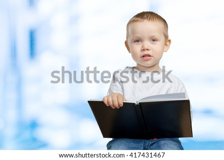 A young school boy is holding a blue book - stock photo