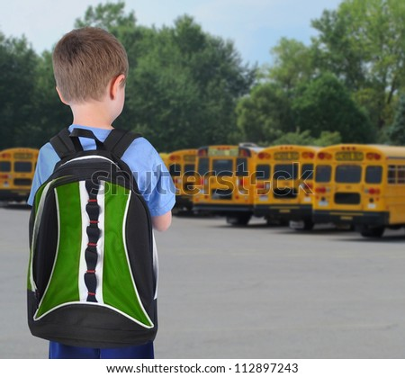 A young school boy is standing with a book bag and looking at school buses in the background. - stock photo
