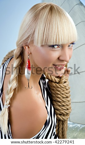 A young seafarer is ready to a new cruise. Spoon-bait as a earring. - stock photo
