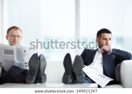 A young serious businessman with newspaper looking at camera with his pensive colleague sitting near by - stock photo