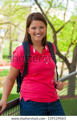 A Young, smiling college student outside - stock photo