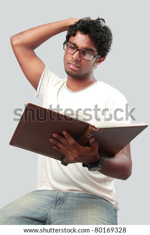 A young student gets bored while reading his note book - stock photo