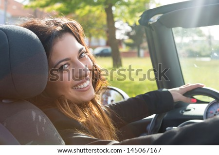 A young successful business woman in a luxurious convertible sports car - stock photo