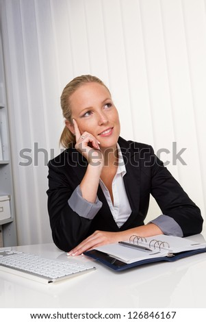 a young, successful business woman sitting at her desk in the office - stock photo