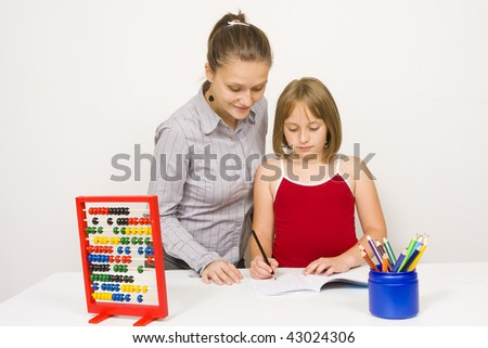 A young teacher or could be mother helping a little girl to learn, both of them paying attention on the little student's action against white wall - colored pencils on the table in a blue recipients. - stock photo