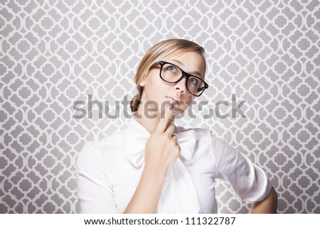 A young teacher or student wearing glasses is in in deep thought while standing in front of a modern pattern. - stock photo