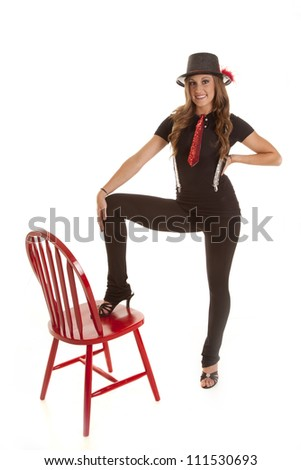 a young teen girl in her jazzy outfit with her hat and tie and suspenders with her foot on a red chair. - stock photo