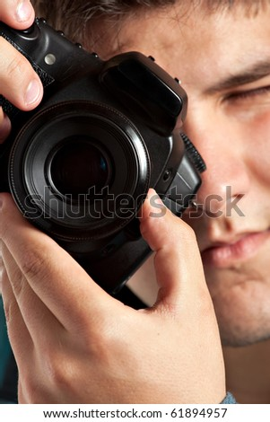A young teenage photographer taking a photo with his DSLR camera. Shallow depth of field. - stock photo