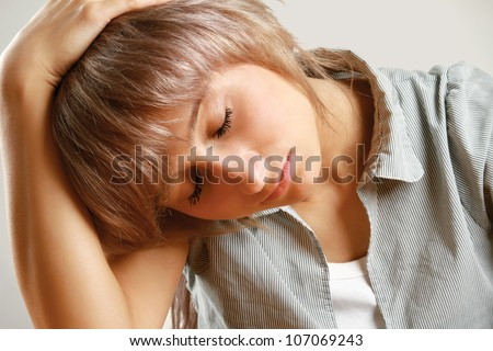 A young tired woman sitting at the desk, isolated on grey background - stock photo