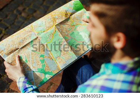 A young tourist with a beard sitting and looks at map of the city, close-up - stock photo