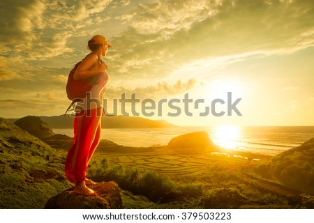 A young traveller looking at sunset on the island Lombok, Indonesia. Traveling along Asia, active lifestyle concept - stock photo