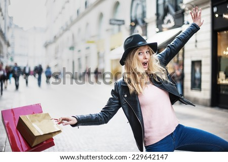 a young trendy woman doing shopping in the city expresses its joy in jumping and laughing - stock photo