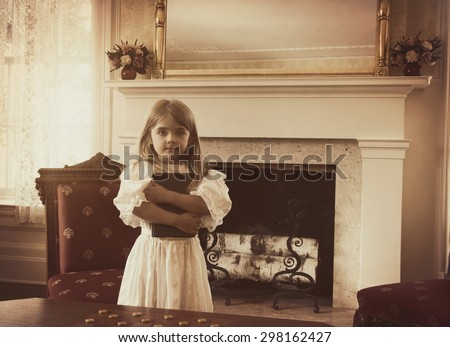 A young vintage child is holding a reading book inside an old fashioned home for an education or generation concept. - stock photo