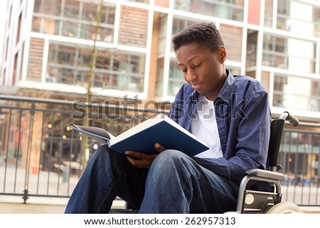 a young wheelchair user reading a book. - stock photo
