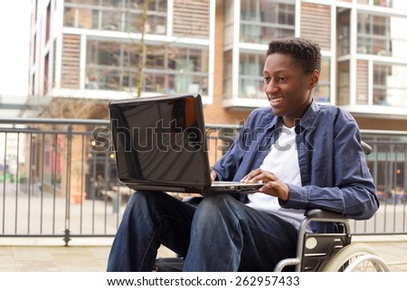 a young wheelchair user working on a laptop. - stock photo