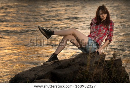 A young white caucasain female sitting on a rock near a river during sunset with her legs up. - stock photo