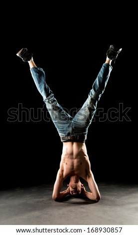 A young white Caucasian male stands on his head upside down doing a yoga inversion in the studio. - stock photo