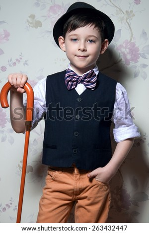 A young wizard with brown cane. A boy is wearing a light t-shirt with black waistcoat. The hat and striped bow tie complete his look. - stock photo