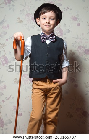 A young wizard with brown cane. A boy is wearing a light t-shirt with black waistcoat. The hat and striped bow tie complete his look - stock photo