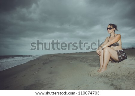 A young woman alone on the beach with a storm brewing on the horizon - stock photo