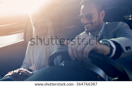 A young woman and a young man are laughing in the car, enjoying in the road trip. - stock photo