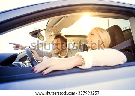 A young woman and a young man are laughing in the car, enjoying in the road trip. The woman is driving. - stock photo