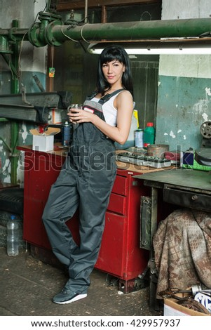 a young woman as a mechanic in a garage. rare professions for women. girl mechanic have a coffee break and resting. - stock photo