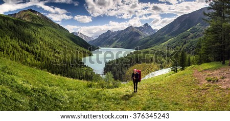 A young woman backpacker is resting after along hike with a mountain lake. - stock photo