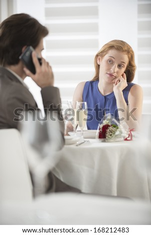 a young woman bored at the restaurant while her husband phone - stock photo