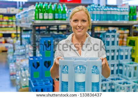 a young woman buys bottled water in the beverage department at the grocery store. - stock photo