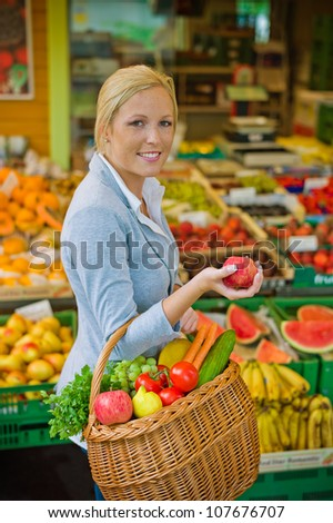 a young woman buys fruits and vegetables at a market. fresh and healthy food. - stock photo