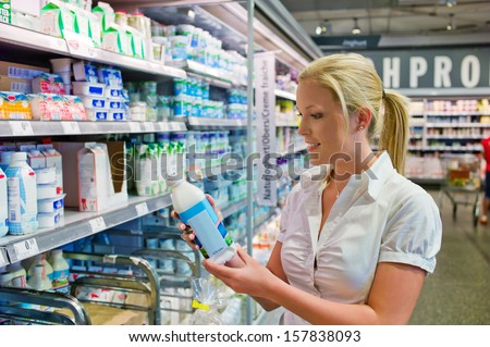 a young woman buys milk in a supermarket. fresh food from the refrigerated section - stock photo