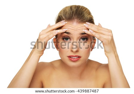 A young woman checking wrinkles on her forehead - stock photo