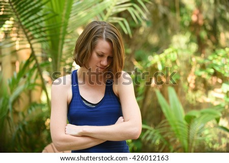 A young woman crying with arms crossed across chest because of stress - stock photo