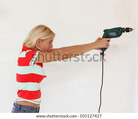 A young woman drilled a hole in a wall - stock photo