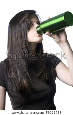 A young woman drinking out of a reusable water bottle. - stock photo