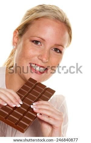 a young woman eating a chocolate bar enjoyable - stock photo