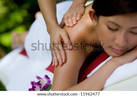 A young woman enjoying a massage outside - stock photo