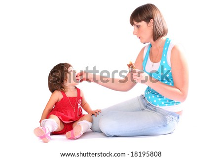 A young woman feeding a pretty girl over white background - stock photo