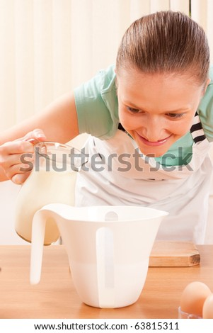 A young woman filling a measuring bowl with milk. - stock photo