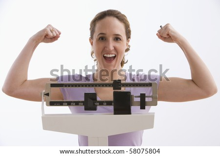 A young woman flexes her arms while standing on a scale and smiling at the camera. Horizontal shot. Isolated on white. - stock photo