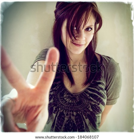 A young woman giving a peace sign with her fingers, instagram style - stock photo