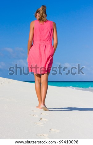 A young woman goes on a coastline - stock photo