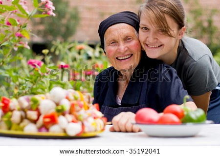 A young woman - grandchild or carer - next to an old woman at the table, with fresh food in front of them. - stock photo
