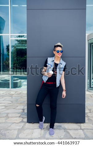 A young woman having a coffee on the go in the city. City girl on the move - stock photo